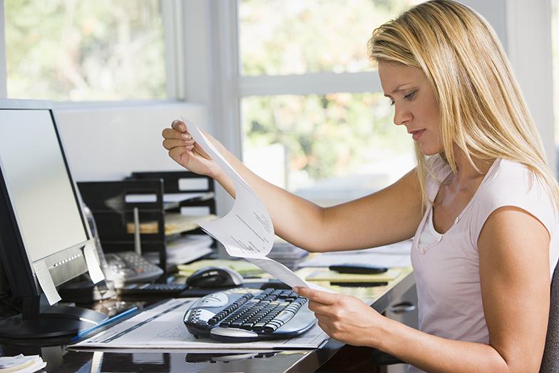 Arbeitsplatz/Büro/junge Frau an Schreibtisch/liest Unterlagen
